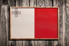 Wooden Malta flag. 3d rendering of Malta flag on a wooden frame over a planks wall Stock Photo