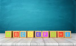 3d rendering of a many colorful toy blocks with letters of the English alphabet in one long line on a wooden desk. Royalty Free Stock Photo