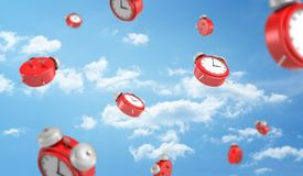 3d rendering of a many red retro-looking alarm clocks with metal bells fall down on cloudy sky background. All time in life. Schedule and planning. Important Royalty Free Stock Image