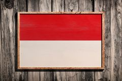 Wooden Monaco flag. 3d rendering of Monaco flag on a wooden frame over a planks wall Royalty Free Stock Photos