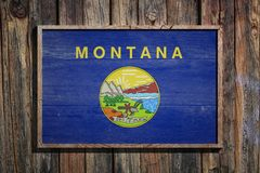 Wooden Montana flag. 3d rendering of a Montana State USA flag on a wooden frame and a wood wall Royalty Free Stock Photo