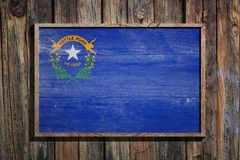 Wooden Nevada flag. 3d rendering of a Nevada State USA flag on a wooden frame and a wood wall Stock Photography
