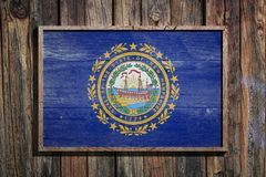 Wooden New Hampshire flag. 3d rendering of a New Hampshire State USA flag on a wooden frame and a wood wall Stock Images