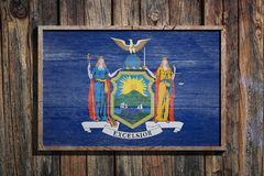 Wooden New York flag. 3d rendering of a New York State USA flag on a wooden frame and a wood wall Stock Image