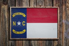 Wooden North Carolina flag. 3d rendering of a North Carolina State USA flag on a wooden frame and a wood wall Stock Photo