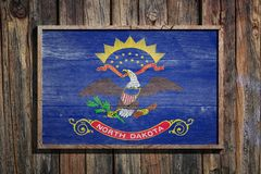 Wooden North Dakota flag. 3d rendering of a North Dakota State USA flag on a wooden frame and a wood wall Royalty Free Stock Photos