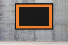 3d rendering from orange picture frame  with a black border on a concrete wall. A 3d rendering from orange picture frame  with a black border on a concrete grey Royalty Free Stock Images
