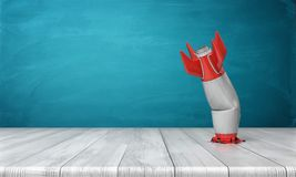 3d rendering of a red and silver realistic model of a retro rocket stands crashed into a wooden desk on a blue. Background. Failed launch. Technological Royalty Free Stock Photo