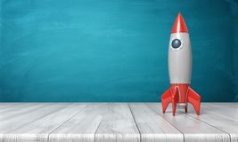 3d rendering of a red and silver realistic model of a retro rocket stands on a wooden desk on a blue background. Royalty Free Stock Images