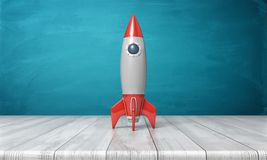 3d rendering of a red and silver realistic model of a retro rocket stands on a wooden desk on a blue background. Stock Image