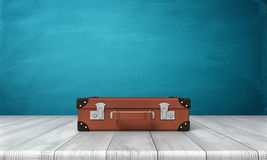 3d rendering of single closed and buckled brown suitcase resting on a wooden desk. With a blue background. Travelling and packing. Business suitcase. Heavy Stock Image