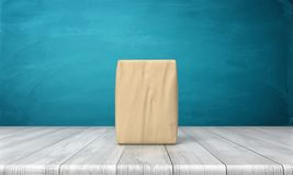 3d rendering of a single closed cement bag vertically placed on a wooden desk on blue background. 3d rendering of a single closed cement bag vertically placd on Royalty Free Stock Images