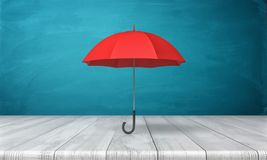 3d rendering of a single red classic umbrella with an open canopy standing above a wooden desk on blue background. Royalty Free Stock Photo