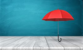 3d rendering of a single red classic umbrella with an open canopy standing above a wooden desk on blue background. Business insurance. Safety measures. Hide Stock Photos