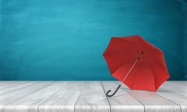 3d rendering of a single red open umbrella lying on its side with an open canopy on a wooden surface on blue background. Royalty Free Stock Images