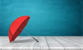3d rendering of a single red open umbrella lying on its side with an open canopy on a wooden surface on blue background. Royalty Free Stock Photo