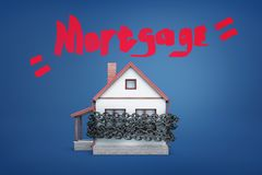 3d rendering of a small family house bound by a metal chain under the red word Mortgage. stock photo