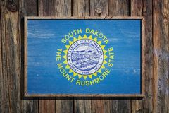 Wooden South Dakota flag. 3d rendering of a South Dakota State USA flag on a wooden frame and a wood wall Royalty Free Stock Photography