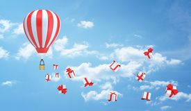 3d rendering of a striped red and white hot air balloon flies in the sky leaving a trail made of many gift box. Holiday period. Gifts from travel. Sale and stock photo