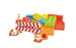 3d rendering of a striped roadblock sign beside several traffic cones standing in front of a colorful lego blocks pile. Stock Photo