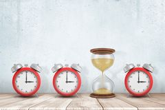 3d rendering of three alarm clocks and one sandglass on white wooden floor with white wall background stock images