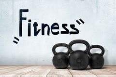 3d rendering of three black kettlebells on white wooden floor with FITNESS sign above on white wall background stock image