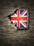 Old United Kingdom flag in brick wall. 3d rendering of an United Kingdom flag over a rusty metallic plate embedded on an old brick wall Royalty Free Stock Photography