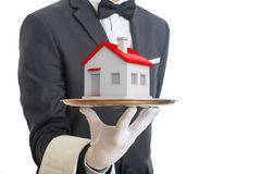 3d rendering waiter offering a house. On a tray Stock Photo