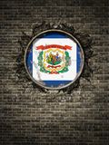 Old West Virginia flag in brick wall. 3d rendering of a West Virginia State flag over a rusty metallic plate embedded on an old brick wall stock illustration