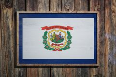 Wooden West Virginia flag. 3d rendering of a West Virginia State USA flag on a wooden frame and a wood wall Royalty Free Stock Photography