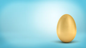 3d rendering of a whole golden egg with metallic reflection on blue background. Stock Photos