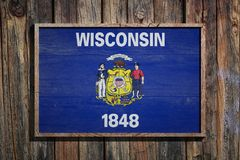 Wooden Wisconsin flag. 3d rendering of a Wisconsin State USA flag on a wooden frame and a wood wall Stock Image