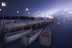 3d rendering wood pier near sea with lamp post and boat in twilight scene. 3d rendering wood pier near sea with lamp post and boat Stock Images