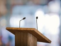 Podium with microphone. 3d rendering wooden podium with microphone on blurred background royalty free stock photos