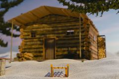 3d rendering of wooden sledge covered with snow in front of log. Cabin Stock Photography
