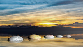 3D rendering of Zen stones in water with sunset sky Royalty Free Stock Photo