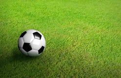 3D rendeu a bola de futebol preto e branco no futebol verde do futebol Fotografia de Stock
