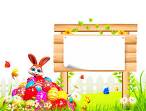 Coelhinho da Páscoa de Brown que senta-se na pilha dos ovos Imagem de Stock