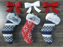 3D rinden de calcetines rojos y azules hermosos de la Navidad con las cintas Imagen de archivo