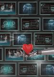 3D robot hand holding a heart against background with medical interfaces. Digital composite of 3D robot hand holding a heart against background with medical Royalty Free Stock Photos