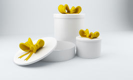 3D round gift boxes with yellow bow. 3D rendering. Three blank 3D round gift boxes with yellow bow over gray background. 3D rendering Stock Photos