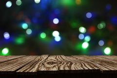 3D rustic wooden table against Christmas bokeh lights background Royalty Free Stock Photo