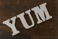 3D segna l'ortografia con lettere dell'YUM Over Wooden Background Immagini Stock