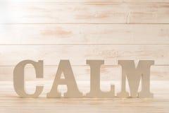 3D segna l'ortografia con lettere della CALMA sopra il fondo di legno del pannello Fotografia Stock Libera da Diritti