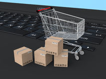 3d shopping cart and cartons on a laptop Royalty Free Stock Image