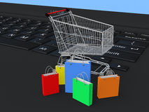 3d shopping trolley and bags on laptop Royalty Free Stock Image