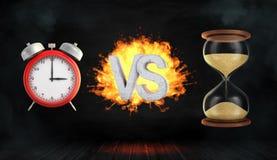 3d som framför ett stort flammande ord VS ställningar mellan en röd retro ringklocka och ett timglas Arkivfoto