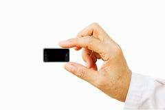 Dé sostener el teléfono elegante móvil muy pequeño con la pantalla negra Es Imágenes de archivo libres de regalías