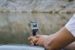 Dé sostener la pequeña cámara de la acción con el caso impermeable Fotos de archivo libres de regalías