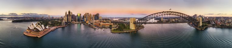 D SYdney From Kirrib Ultra Wide pink rise. Ultra wide 270 degrees aerial panorama of Sydney city CBD landmarks on shores of Sydney harbour at sunrise under pink royalty free stock photography